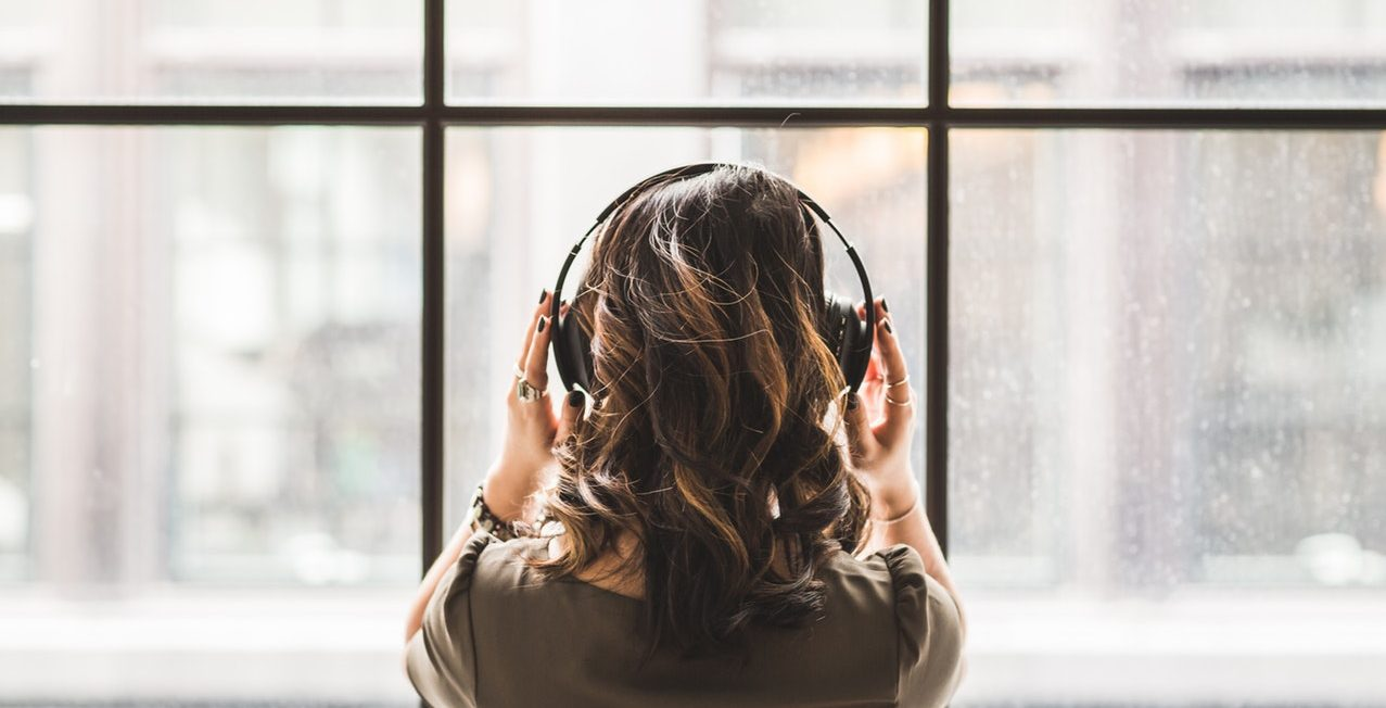 woman with headphone facing a window with her back to viewer