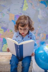 little girls in blue, sitting in bed, reading a large book, with a globe and the world map as background