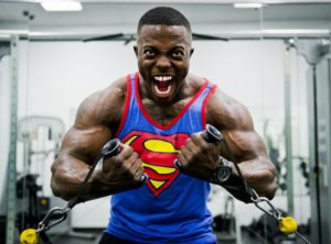 man wearing a superman shirt training weight training in gym