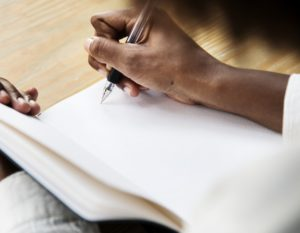 open notebook, hands holding a pen ready to write on it
