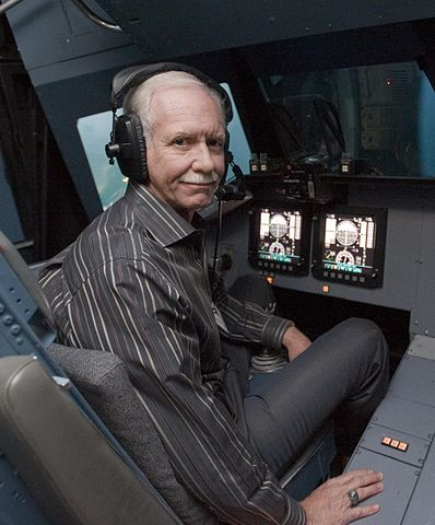 Captain Sully in the vertical motion simulator, wearing headphones and looking at the camera