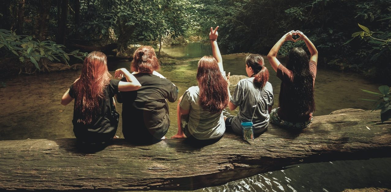 learning inpartof life, five girls sitting on a log